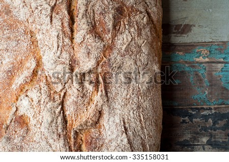 Freshly baked sour dough rye bread loaf served on a rustic wooden table. - stock photo