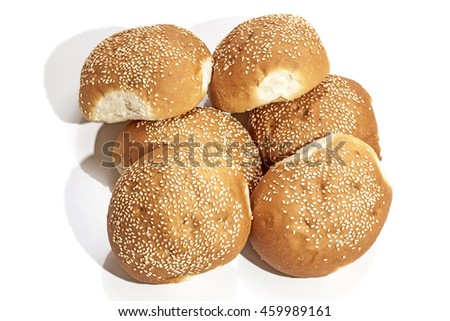 Freshly baked Stack of six golden crisp bread rolls covered with sesame seeds on white background