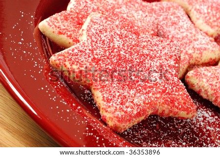 Freshly baked star shaped cookies sprinkled with red and white sugar.  Macro with shallow dof. - stock photo