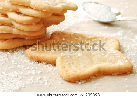 Freshly baked star shaped sugar cookies with spoonful of decorating sugar.  Macro with shallow dof. - stock photo