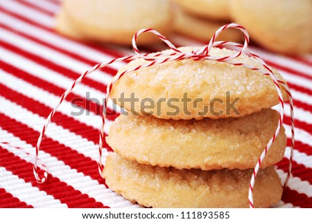 Freshly baked sugar cookies tied with festive baker's twine and stacked on red and white striped placemat.  Macro with extremely shallow dof. - stock photo