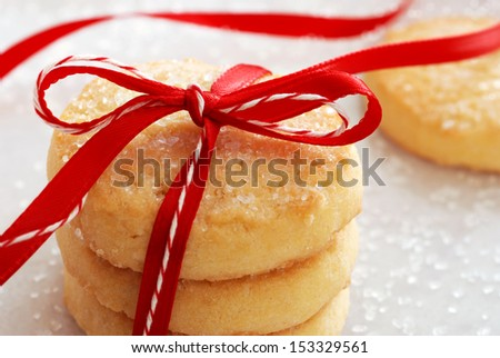 Freshly baked sugar cookies tied with festive bakers twine and red satin ribbon.  Decorating sugar crystals sprinkled in background.  Macro with shallow dof. - stock photo
