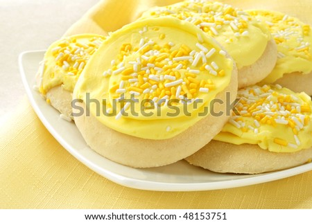 Freshly baked sugar cookies with lemon frosting and sprinkles.  Macro with shallow dof. - stock photo