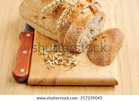 Freshly baked traditional bread on wooden board - stock photo