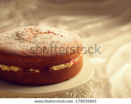 Freshly baked Victoria sponge cake filled with jam and buttercream - stock photo
