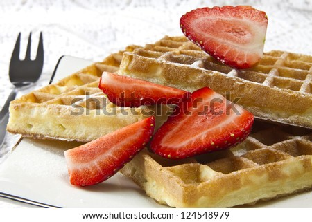 Freshly baked waffles with strawberries - stock photo