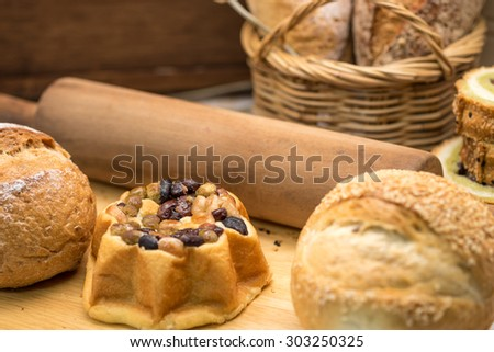 Freshly baked whole grain wheat bread and loaf with rolling pin on wooden cutting board for healthy diet background  - stock photo