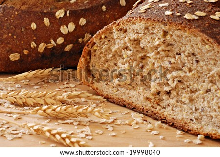 Freshly baked whole grain wheat bread with wheat spikes.  Macro with shallow dof. - stock photo