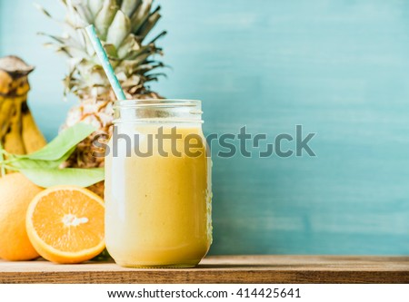 Freshly blended yellow and orange fruit smoothie in glass jar with straw. Turquoise blue background, copy space - stock photo