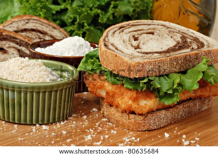 Freshly breaded and deep fried cod fillet on marble rye bread with lettuce on wooden cutting board.  Seasoned breadcrumbs and flour included in composition.  Macro with shallow dof. - stock photo
