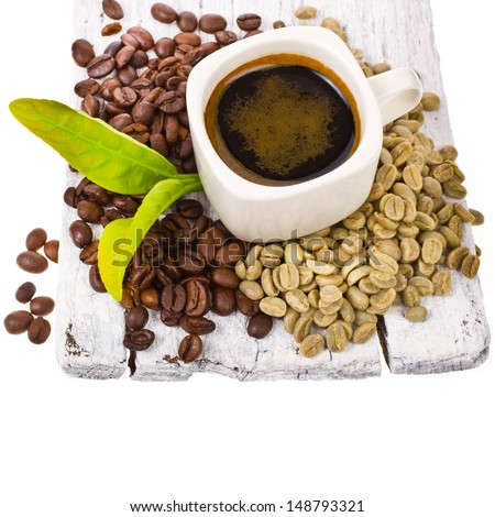 freshly brewed black coffee in a white cup and grain unground coffee on white boards - stock photo