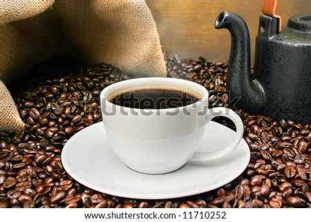 Freshly brewed coffee over dark roasted coffee beans - stock photo