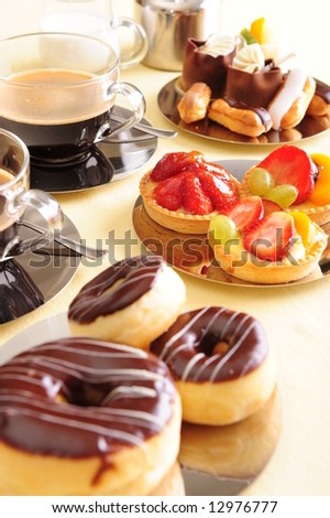 Freshly brewed coffee with a selection of cakes and confectionery. - stock photo