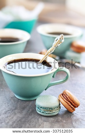 Freshly brewed coffee with delicious macarons. Extreme shallow depth of field with selective focus on chocolate macaron. - stock photo