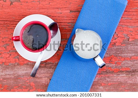 Freshly brewed cup of black coffee in a red mug on a white saucer served with a jug of milk and blue napkin on a grunge wooden rustic red picnic table with flaking paint, view from above - stock photo
