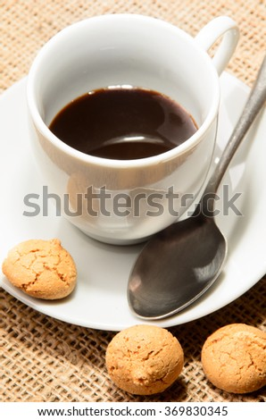 freshly brewed espresso in a cup and home made biscuit