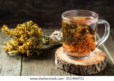 Freshly brewed tea with useful dried St. John's wort in a glass mug on a wooden table. Selective focus - stock photo
