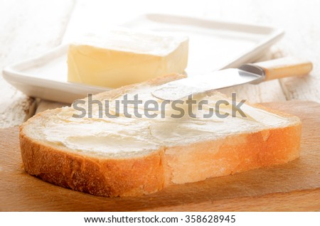 freshly buttered slice of bread and knife - stock photo