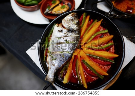 Freshly caught golden spar is fried in a pan with vegetables, the waiter brought the fish in a pan with vegetables and mussels for a snack - stock photo