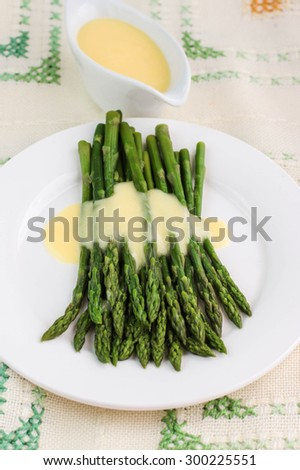 freshly cooked green asparagus with hollandaise sauce. Selective focus