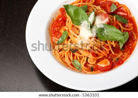 Freshly cooked plate of spaghetti with tomato sauce and oregano - stock photo