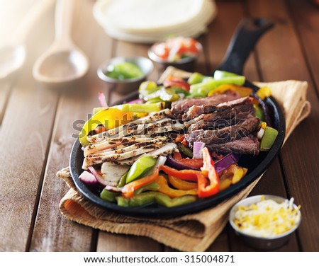 freshly cooked spicy hot mexican steak and chicken fajitas in cast iron pan