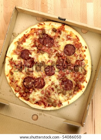 Freshly cooked takeaway pizza on a kitchen bench - stock photo