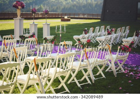 Freshly cut beautiful red and purple wedding flowers garland on chair at aisle - stock photo