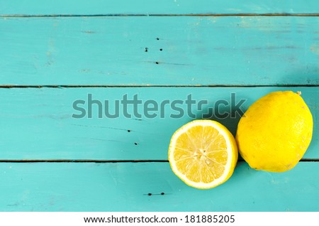Freshly cut half and whole lemons on rustic boards. - stock photo