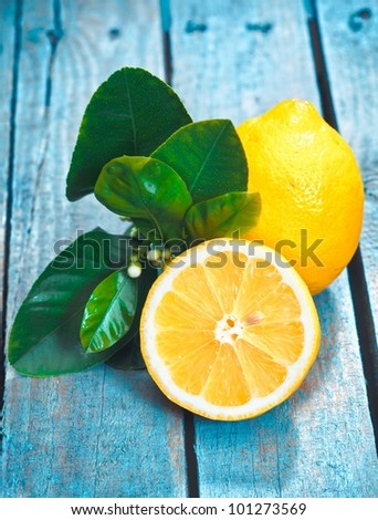Freshly cut half and whole lemons with leaves on rustic boards - stock photo