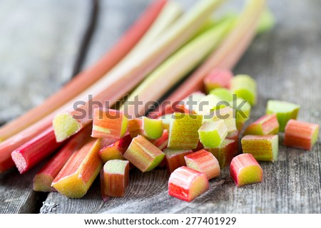 freshly cut pieces of rhubarb on wooden surface - stock photo