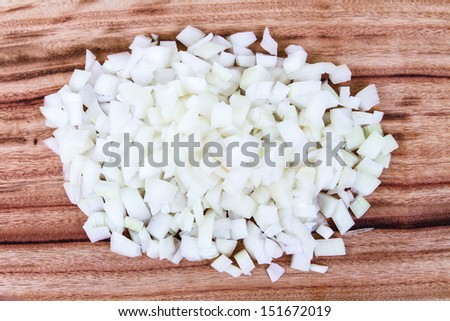 Freshly Diced White Onion. A new pile of chopped white onion on a wooden chopping board - stock photo