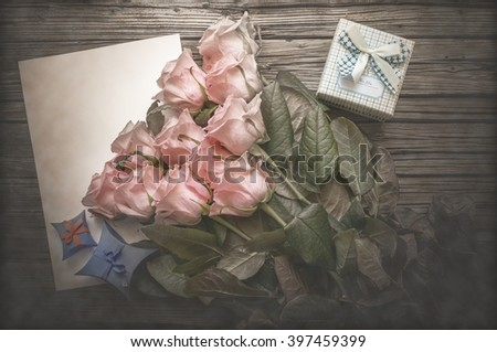 Freshly gathered pink stemmed roses on top of blank white paper with pretty little bowed gift box over weathered wooden background - stock photo