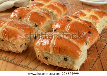 Freshly glazed hot cross buns on a cooling rack - stock photo