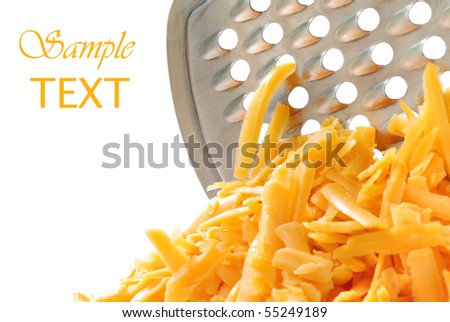 Freshly grated cheddar cheese with stainless steel grater on white background.  Macro with shallow dof. - stock photo