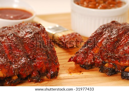 Freshly grilled barbecue spare ribs with beans and dipping sauce