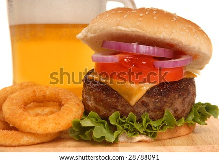 Freshly grilled cheeseburger with onion rings and a cold beer - stock photo
