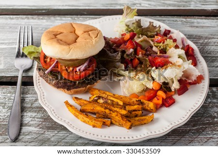 Freshly grilled hamburger with cheddar cheese, organic tomatoes and lettuce, red onion, dill pickle and toasted bun with homemade oven baked sweet potato fries with an organic salad on the side top - stock photo