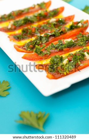 freshly grilled red pepperoni with anchovies fillet and green sauce - stock photo