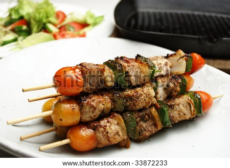 Freshly grilled Shish Kebabs. Grill pan and salad in the background. Shallow depth of field high key shot - stock photo