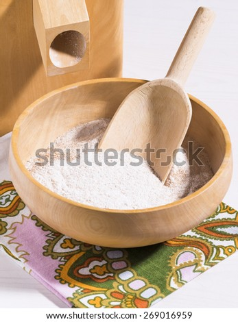 Freshly ground whole meal flower in wood bowl on cloth