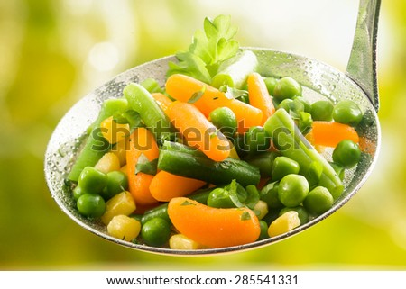 Freshly harvested assorted young vegetables diced and steamed including whole baby carrots, green beans, peas and corn served in a metal kitchen ladle, close up view - stock photo