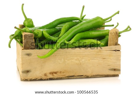 Freshly harvested jalapeno peppers in a wooden crate on a white background