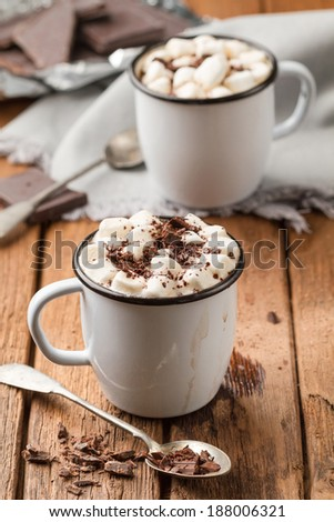 Freshly hot chocolate with marshmallows in two enamel tin mugs - stock photo