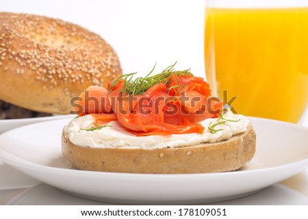 Freshly made bagel with cream cheese, salmon, dill and orange juice on a white background - stock photo
