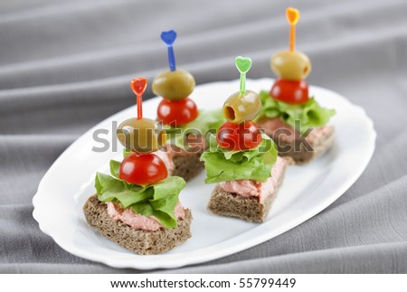 Freshly made bites of lettuce, olives and cherry tomatoes - stock photo