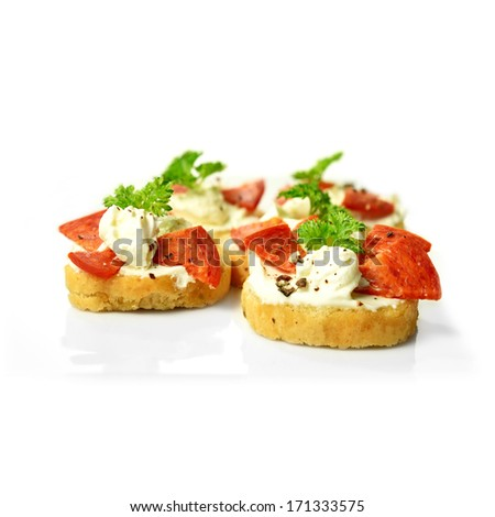 Freshly made cream cheese and pepperoni bruschetta with a parsley garnish against a white background. Copy space. - stock photo
