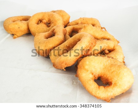 Freshly made doughnuts in a small pile on baking paper - stock photo