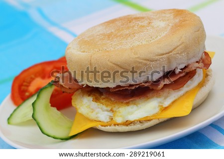 Freshly made egg and bacon muffin on blue background, closeup
