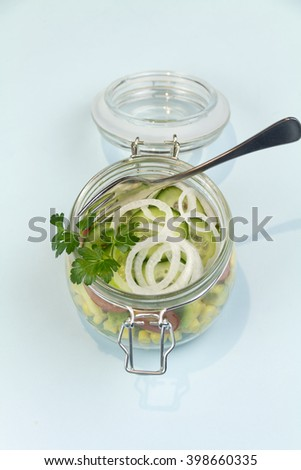 Freshly made garden salad served and presented in a glass jar.